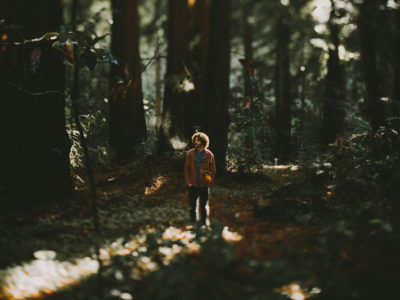 man in middle of forest with breath in the air