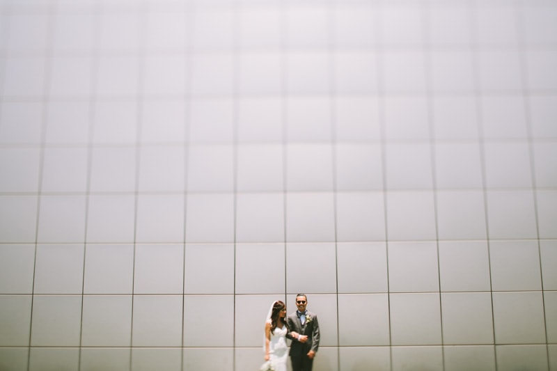 couple standing in front of gray wall