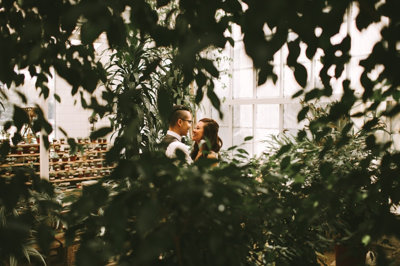 couple snuggling in greenhouse