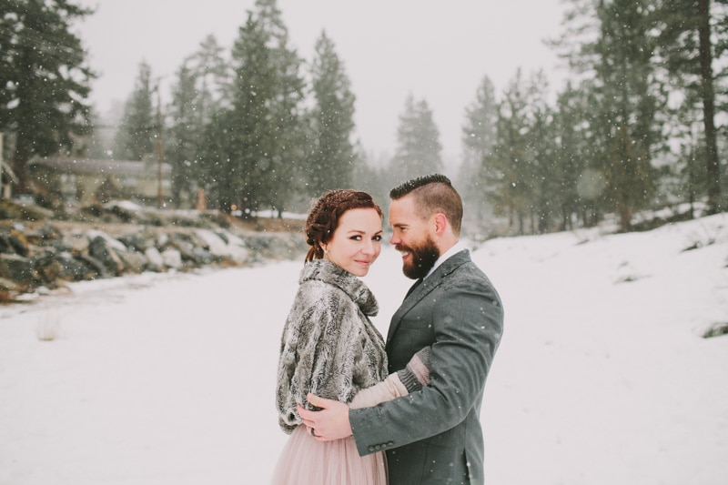 couple standing with snow falling