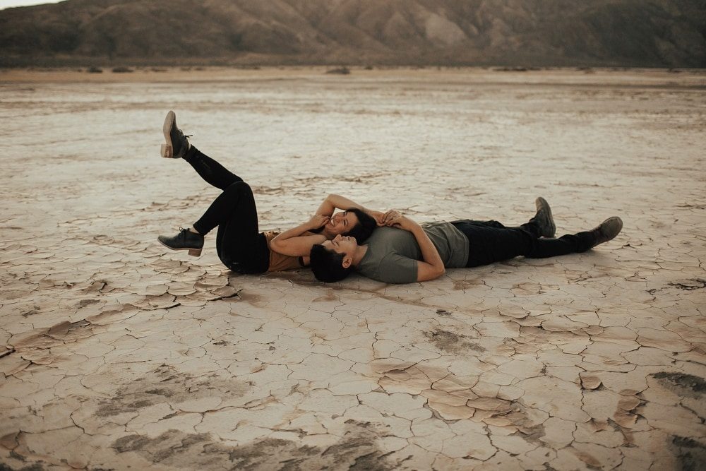 couple laying on a dry lake bed