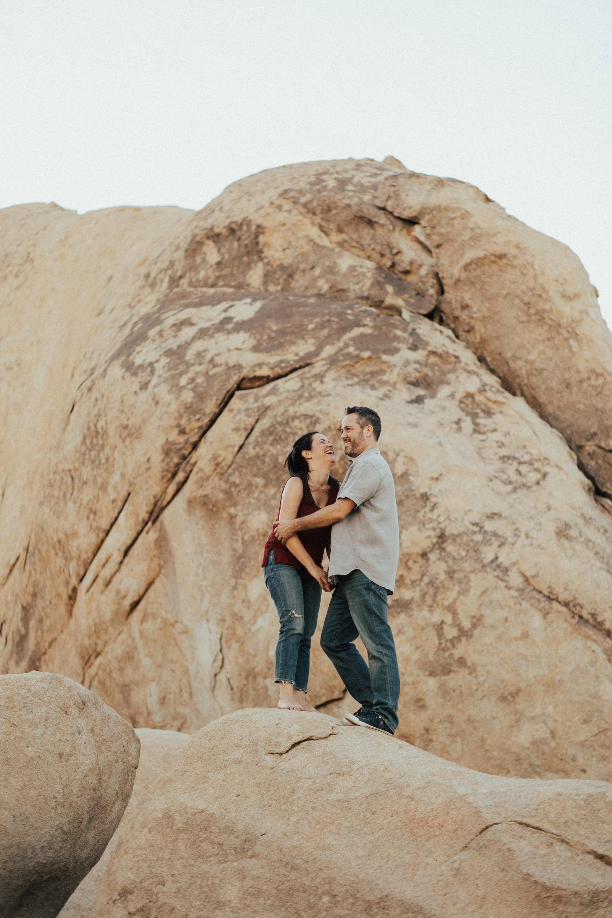 sweet engagement photo of a couple standing on boulders in joshua tree national park