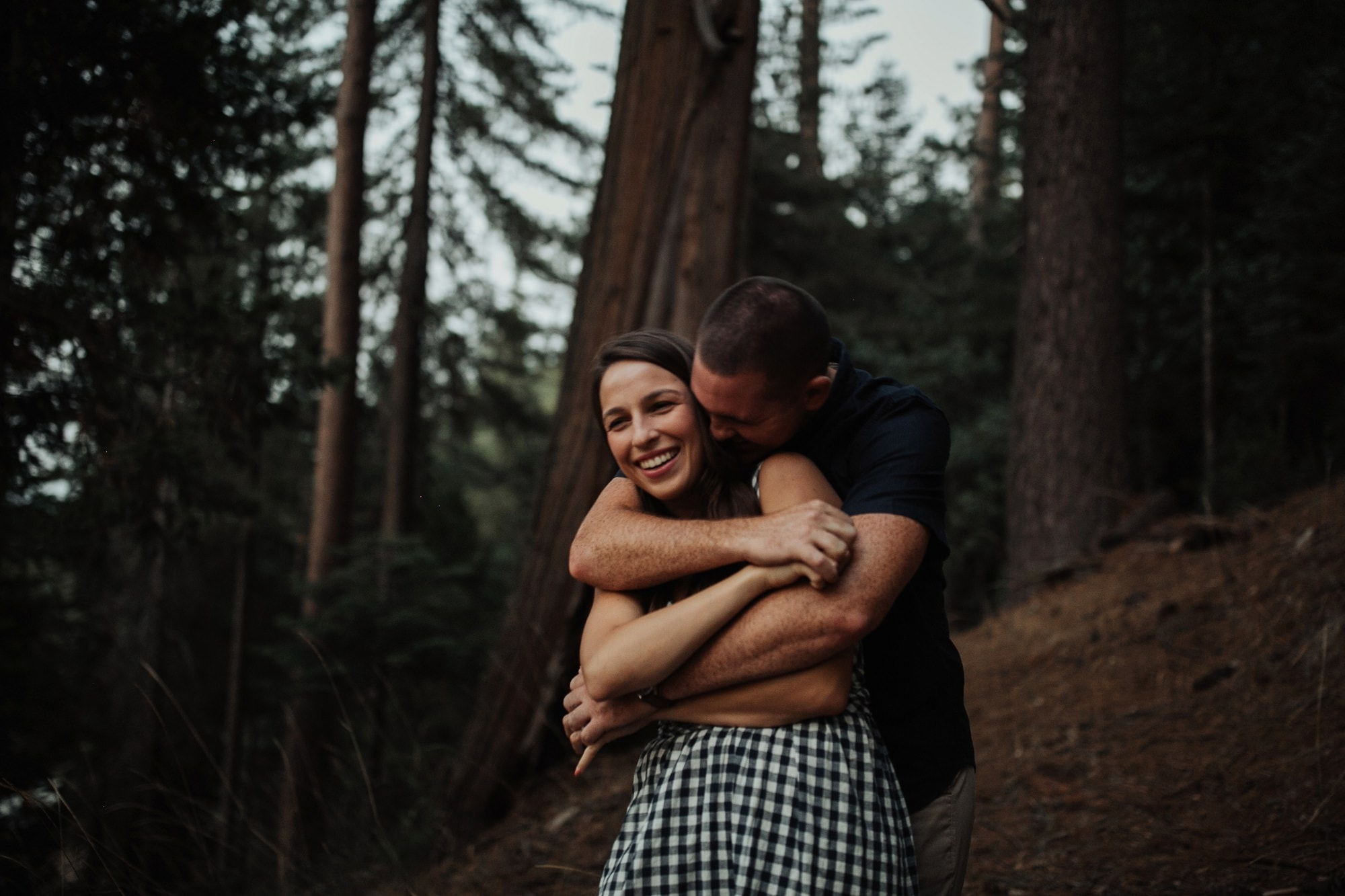couple snuggling in front of trees