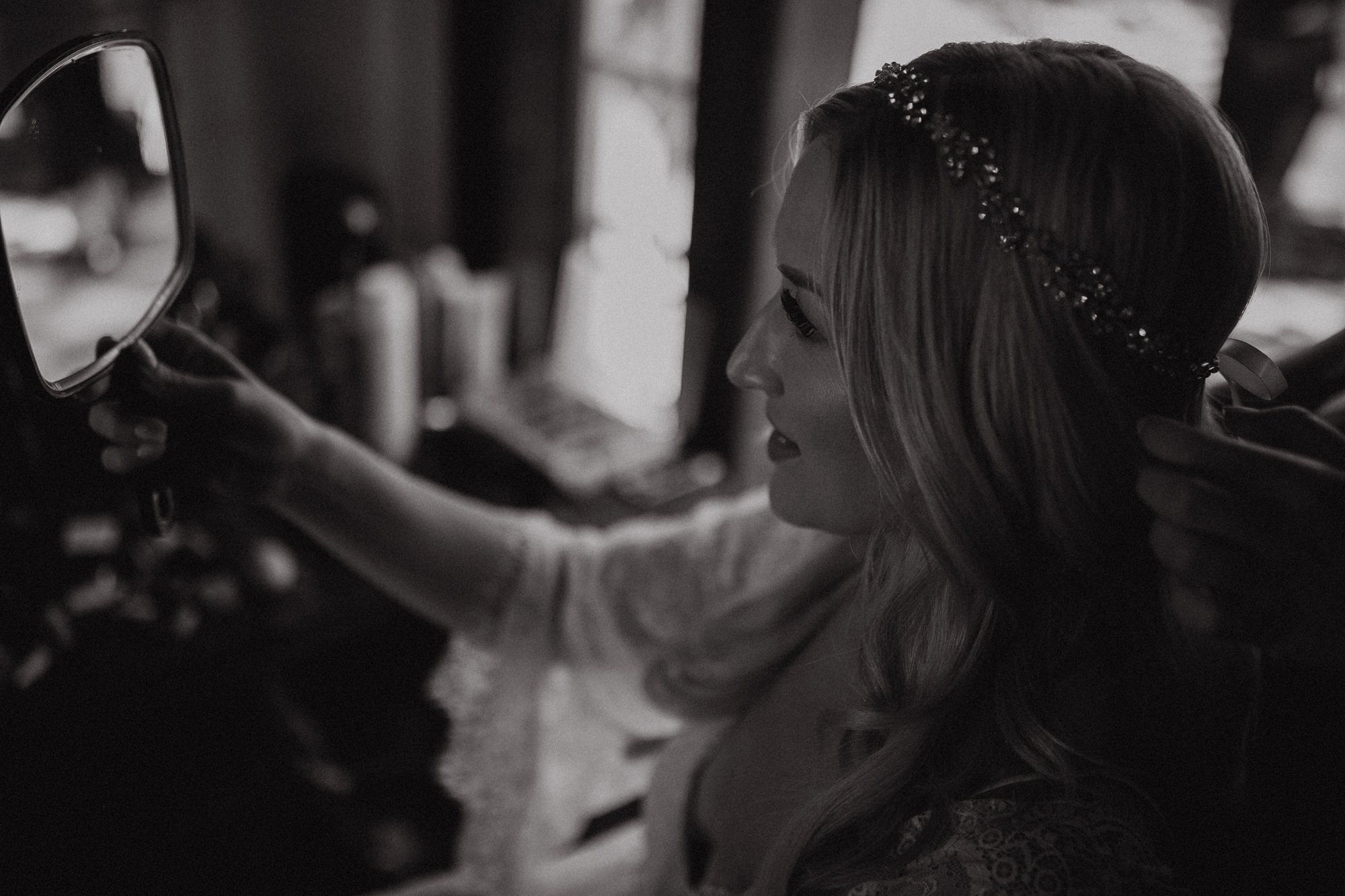 bride holding up mirror while getting her hair done