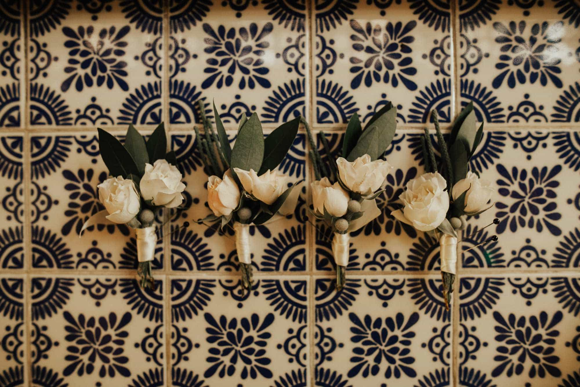 white boutonnieres by beautiful savage flowers