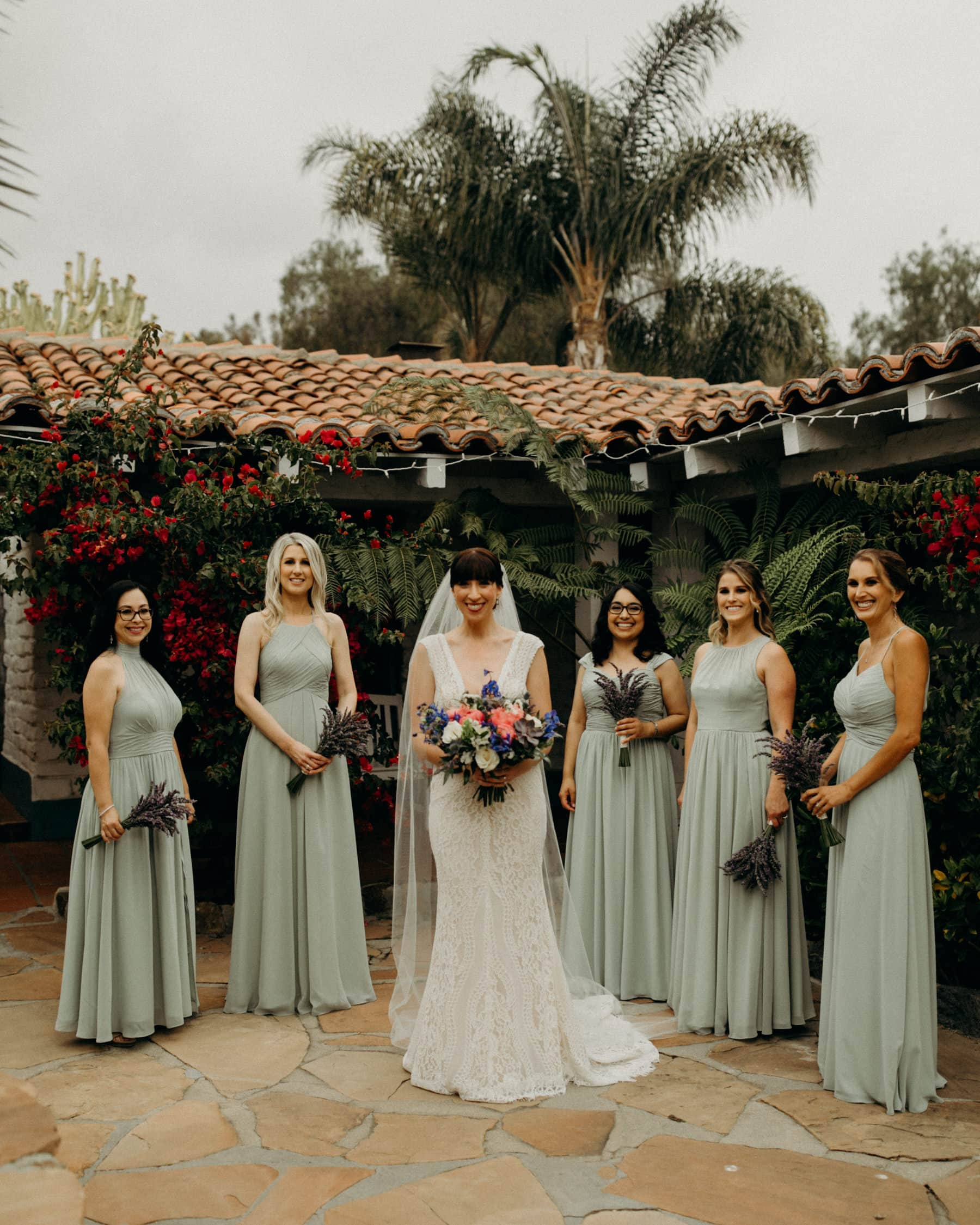 bridesmaids with sage dresses and lavendar bushel bouquets