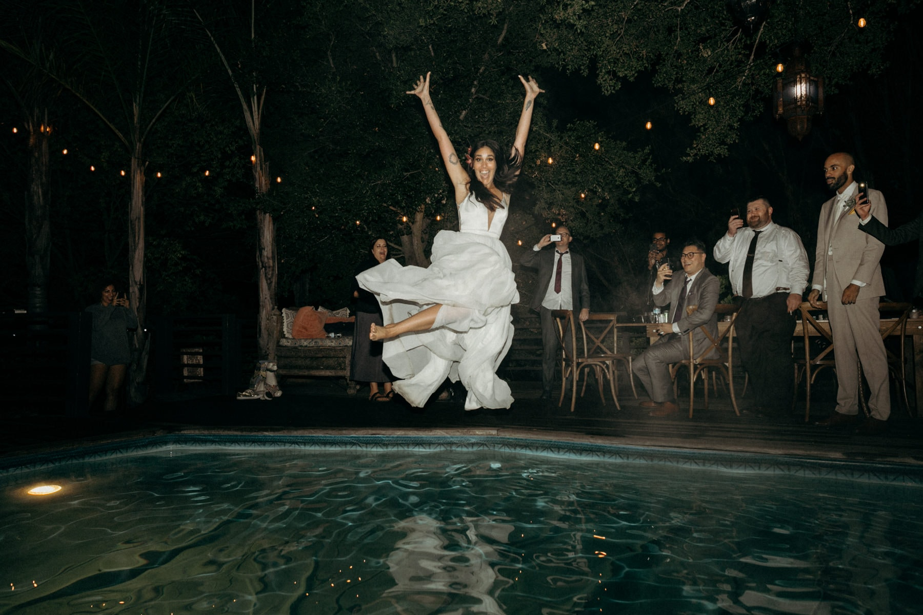 bride jumping in pool with wedding dress